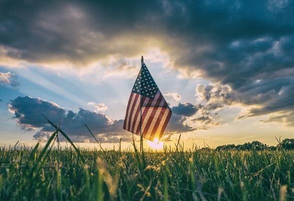 America flag sunrise field Photo by Aaron Burden on Unsplash
